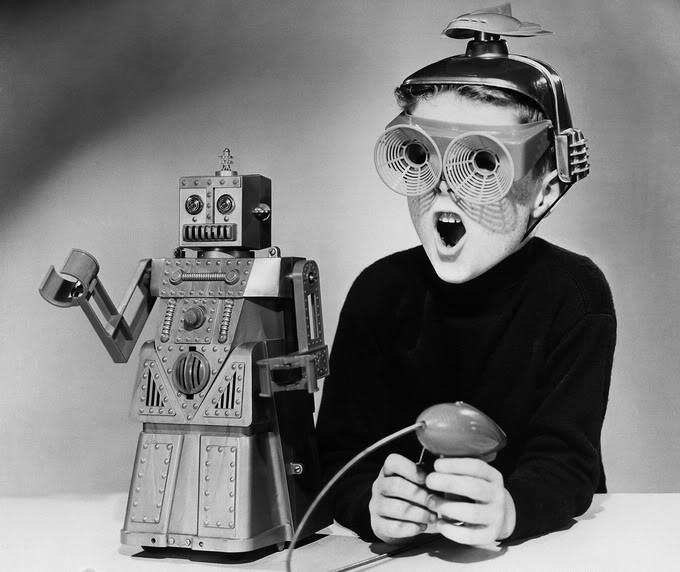 """Original Caption: APRIL 17, 1959. MECHANICAL MAN. NEW YORK. DECKED OUT IN SOME STRANGE-LOOKING HEADGEAR, THIS LAD IS DEMONSTRATING THE TALENTS OF """"ROBERT THE ROBOT,"""" A NEW MECHANICAL TOY. THE ROBOT'S EYES LIGHT UP, HE WALKS, HE TALKS AND MOVES HIS HANDS--ALL VIA REMOTE CONTROL.THE MECHANICAL TOY, MADE BY THE IDEAL TOY CORP., WILL BE DISPLAYED AT THE AMERICAN FAIR IN MOSCOW THIS SUMMER. IT SELLS FOR ABOUT SIX DOLLARS."""